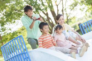 滑り台で遊ぶ4人家族の写真素材 [FYI01298330]