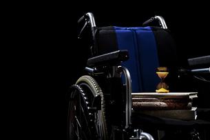 本と砂時計を乗せた車椅子の写真素材 [FYI01298370]