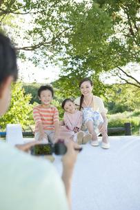 ビデオ撮影する父親と滑り台で遊ぶ家族3人の写真素材 [FYI01298380]