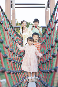 遊具で遊ぶ4人家族の写真素材 [FYI01298382]