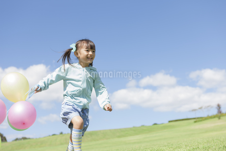 複数の風船を持って走っている女の子の写真素材 [FYI01298390]
