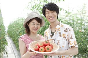 トマトを持っている笑顔のカップルの写真素材 [FYI01298436]
