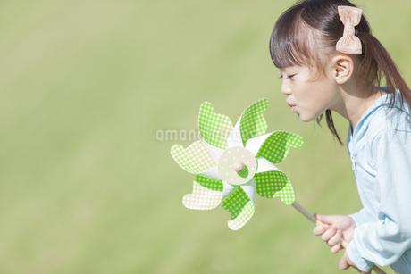 風車で遊ぶ女の子の写真素材 [FYI01298469]