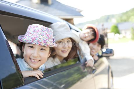 車の窓から身を乗り出す家族4人の写真素材 [FYI01298511]