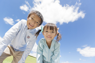 青空の下で笑っている男の子と女の子の写真素材 [FYI01298515]