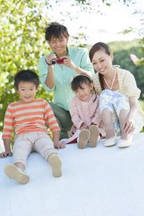 滑り台で遊ぶ4人家族の写真素材 [FYI01298530]