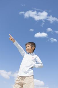 青空の下で指さす男の子の写真素材 [FYI01298533]