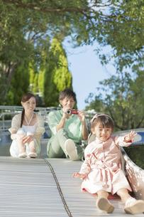 滑り台で遊ぶ家族3人の写真素材 [FYI01298538]