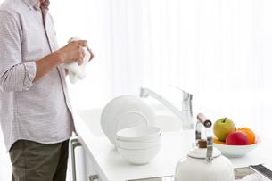 キッチンでお皿を拭く男性の写真素材 [FYI01298656]