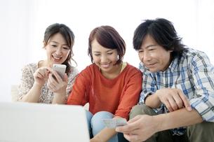 ネットショッピングをする家族3人の写真素材 [FYI01298734]