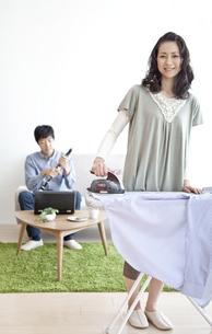 アイロン掛けをする女性とクラリネットを組み立てる男性の写真素材 [FYI01298735]