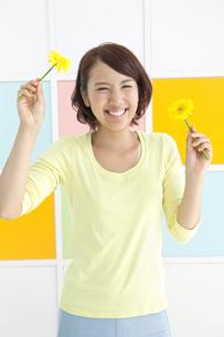 両手に花を持つ笑顔の若い女性の写真素材 [FYI01298751]