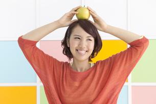 リンゴを頭の上にのせる若い女性の写真素材 [FYI01298761]