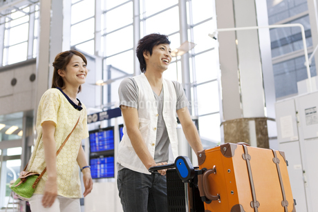 空港を歩くカップルの写真素材 [FYI01298813]
