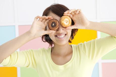 クッキーを持ってはしゃぐ若い女性の写真素材 [FYI01298827]