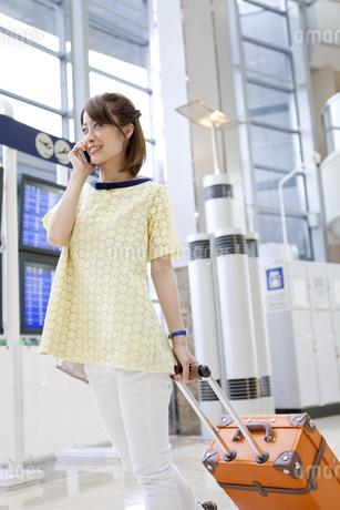 空港で電話をしながら歩く女性の写真素材 [FYI01298832]