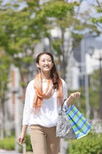 買い物袋を持って歩く中高年女性の写真素材 [FYI01298927]