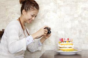 バースデーケーキの写真を撮る女性の写真素材 [FYI01298949]