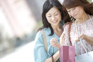 買い物袋を見る中高年女性2人の写真素材 [FYI01298969]
