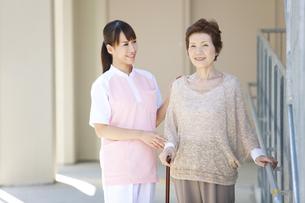 女性介護士と杖をつく中高年女性の写真素材 [FYI01299015]
