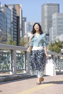 買い物袋を持って歩く中高年女性の写真素材 [FYI01299028]