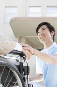 車いすに乗った中高年女性に寄り添う介護士の写真素材 [FYI01299039]