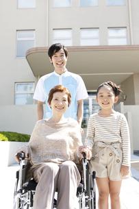 男性介護士と車いすに乗った中高年女性と孫の写真素材 [FYI01299051]