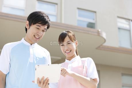タブレットPCを見る男女介護士2人の写真素材 [FYI01299065]