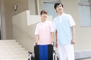 笑顔の男女介護士2人と車いすの写真素材 [FYI01299123]