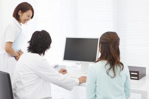 パソコンを見ながら説明する医師と看護師と患者の写真素材 [FYI01299173]