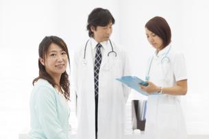 カルテを見ている医師と看護師と笑顔の患者の写真素材 [FYI01299192]