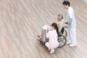 介護士と車いすに乗った中高年男性の写真素材 [FYI01299206]
