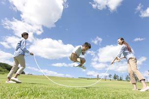 縄跳びで遊んでいる家族3人の写真素材 [FYI01299405]