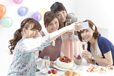 スマートフォンで写真を撮る女性4人の写真素材 [FYI01299455]