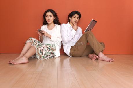 タブレットPCとスマートフォンを操作しているカップルの写真素材 [FYI01299726]