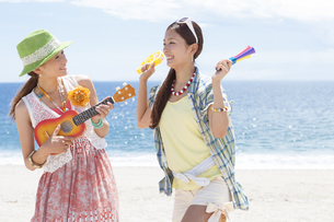 海岸で楽器を持って楽しむ女性2人の写真素材 [FYI01299879]
