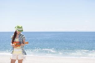 海岸でウクレレを演奏している女性の写真素材 [FYI01299940]