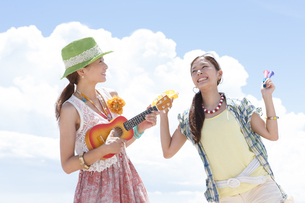 青空の下で楽器を持って楽しむ女性2人の写真素材 [FYI01299960]