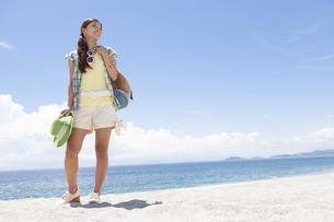 海岸で鞄と帽子を持っている笑顔の女性の写真素材 [FYI01299971]