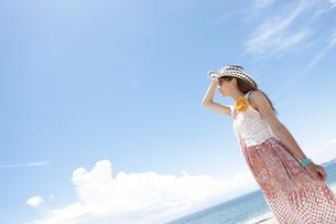 海を眺めているサングラスをかけた女性の写真素材 [FYI01300003]