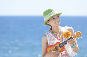 海岸でウクレレを演奏している女性の写真素材 [FYI01300014]