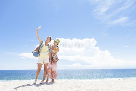 海岸で記念撮影する女性2人の写真素材 [FYI01300015]