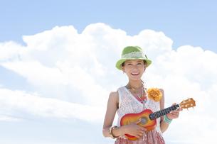 青空の下でウクレレを演奏している女性の写真素材 [FYI01300059]