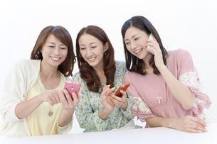 スマートフォンを持つ中高年女性3人の写真素材 [FYI01300101]
