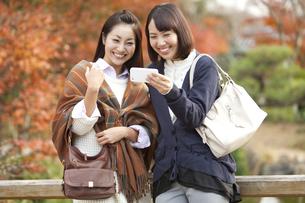 スマートフォンを見ている女性2人の写真素材 [FYI01300202]