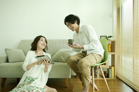 タブレットPCを操作する女性と覗き込む男性の写真素材 [FYI01300229]
