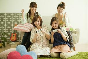 テレビゲームで遊ぶ若い女性4人の写真素材 [FYI01300422]