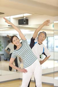 ストレッチをしている笑顔の中高年夫婦の写真素材 [FYI01300434]