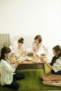 トランプで遊ぶ若い女性4人の写真素材 [FYI01300436]