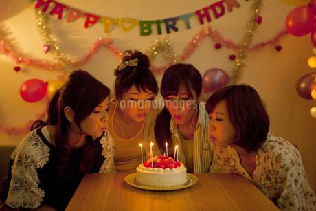 ロウソクのついたケーキを囲む若い女性4人の写真素材 [FYI01300462]